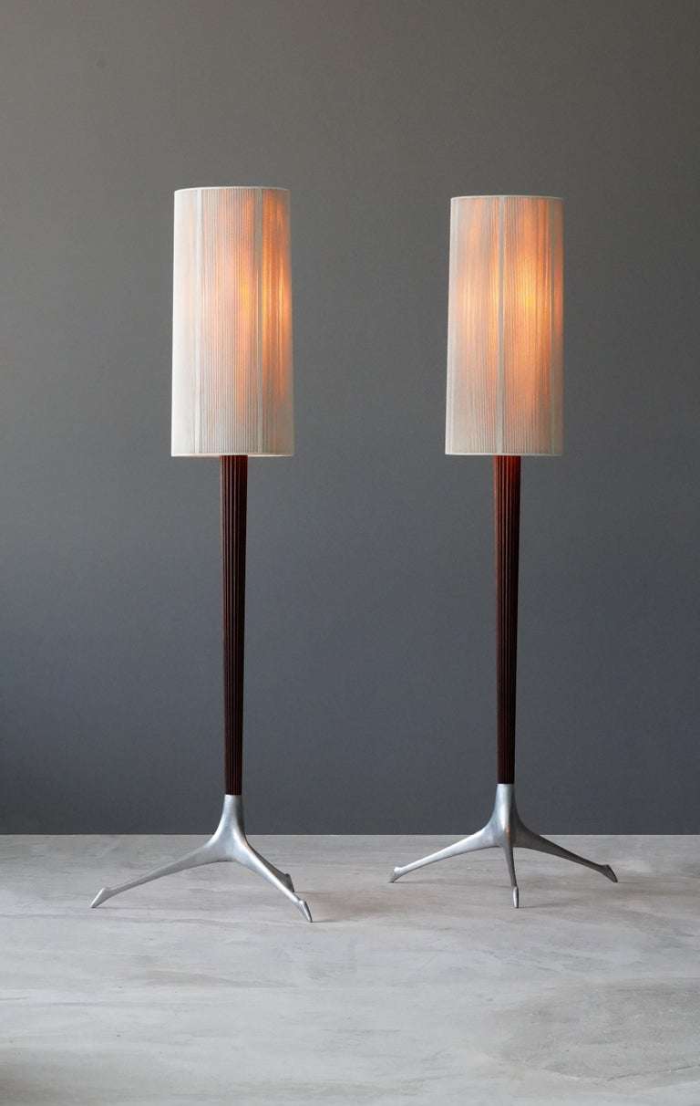 A pair of rare floor lamps, designed by Vladimir Kagan and produced by Kagan-Dreyfus Inc, circa 1958. Cast aluminum is paired with a finely carved mahogany rod, bears original nylon screens.   Other American designers of the period include George