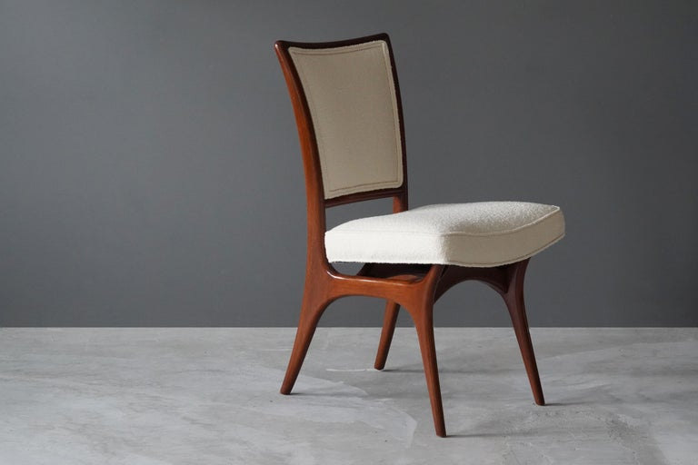 A sculptural organic side chair or dining chair designed by Vladimir Kagan. Organicly carved walnut is paired with a high-end boucle fabric. Marked.