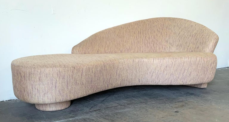 This sofa is absolutely stunning! It's a custom made Postmodern biomorphic / serpentine cloud sofa from the mid-1990s. The sofa features a single disc base with the back extending downward also as a leg.  This sofa is very reminiscent of Vladimir