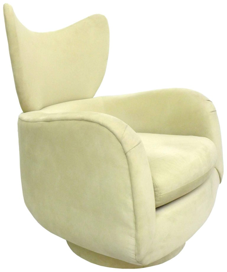 An incredibly stylish and comfortable swivel lounge chair designed by Vladimir Kagan for Directional. A great form with an unusual wing-back detail and its original pale-sage suede upholstery. A wonderfully sculptural and functional seating design