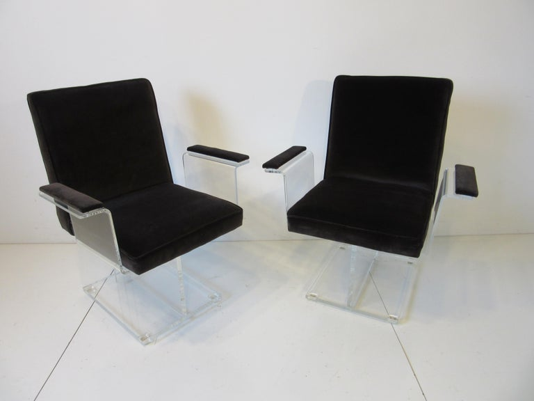 A pair of Kagan Lucite pedestal armchairs upholstered in a dark chocolate velvet fabric having a great sculptural look with matching arm rests. Small Lucite foot pads attached to the square base help protect your floors, a rare form manufactured by