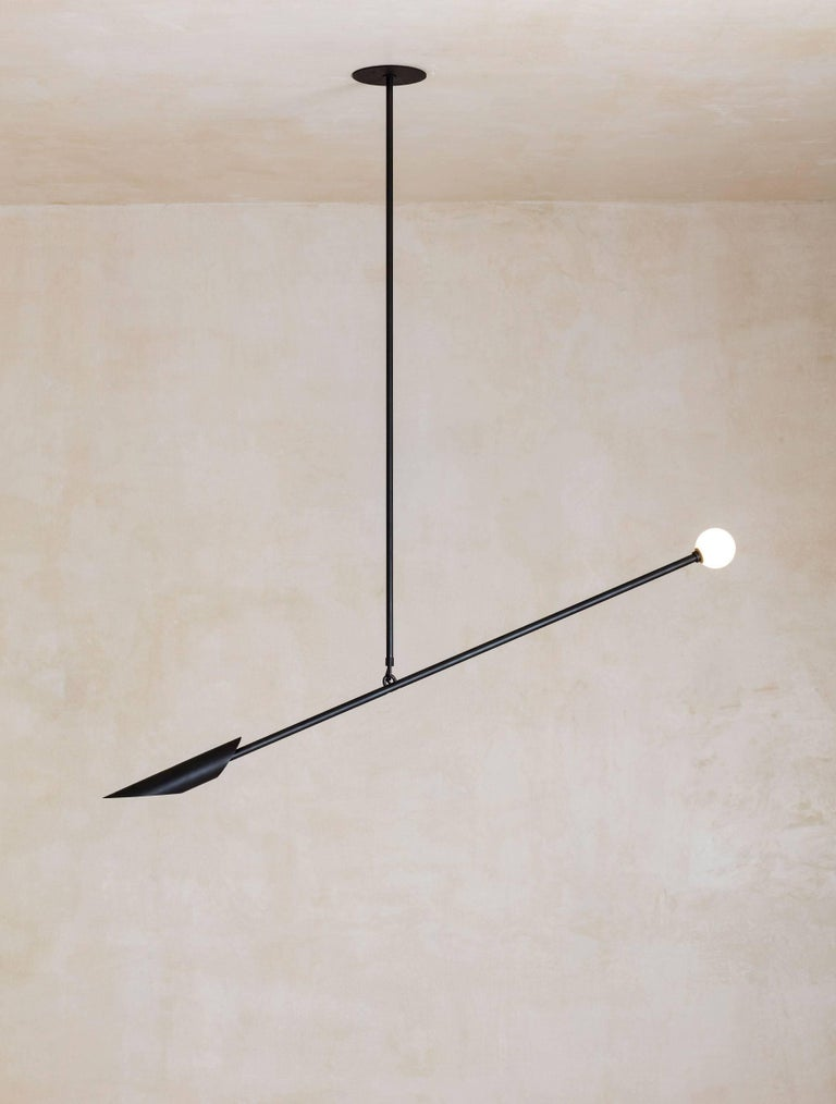 Balancing a sharp brass shade on one side, and a glass orb on the other, the Voyager orb pendant creates a dramatic composition.