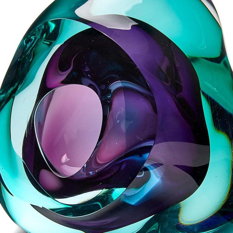 Vug in emerald and purple is a unique hand blown sculpture by the British artist Samantha Donaldson. Created by layers of colored glass in soft emerald green and purple, the transparent colors merge and create further hues throughout the piece. An