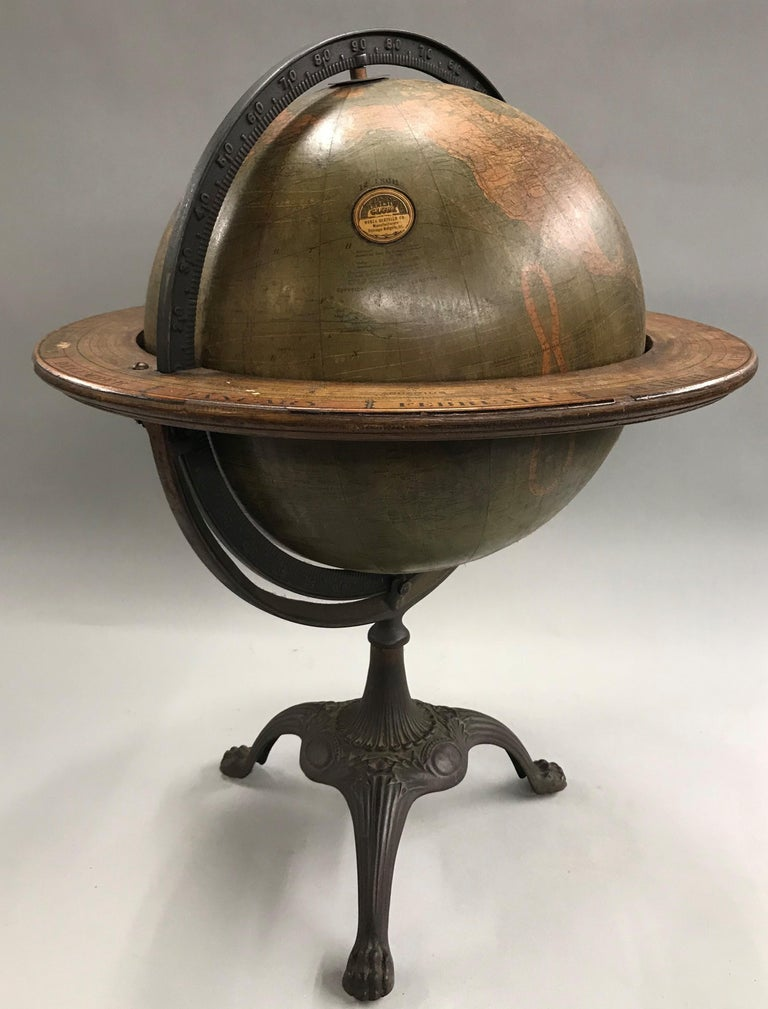 A fine 12 inch terrestrial W. & A.K. Johnston copyright globe by Weber Costello of Chicago Heights, IL with embossed graduated cast iron Meridian ring, wooden horizon ring depicting months and zodiac signs, all supported by a tripod cast stand with