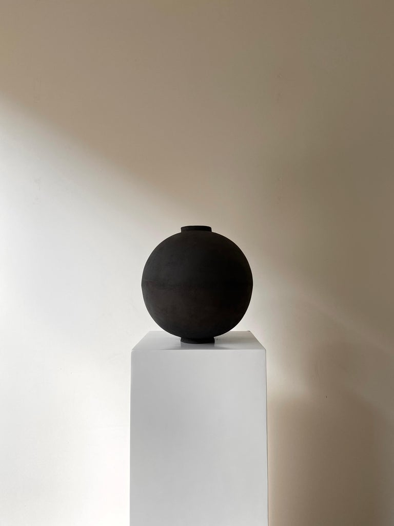 Wabi moon Jar by Laura Pasquino Dimensions: Ø 32 x H 33 cm, opening Ø 8 cm Materials: stoneware ceramic Finishing: natural unglazed exterior, transparent matte glazed interior Colour: black  Laura Pasquino Incorporating references from