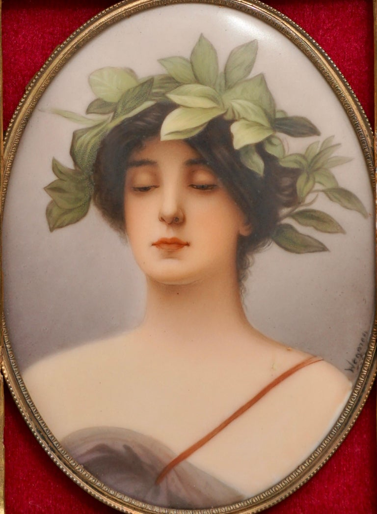 """Shoulder length portrait of young lady in classical gown with laurel leaf wreath in hair. Manufacturer: C.M. Hutschenreuther signed lower right """"Wagner""""  Stamped on back """"12"""" over circle with """"CR"""" with painted titled """"Daphne""""   Oval Porcelain"""