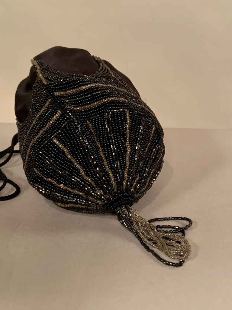 Hand Made in Hong Kong in the 1970's this black satin evening bag has an Art Deco design worked in black and silver caviar beads with a matching beaded tassel.  A woven black cord is used for the drawstring shoulder strap. It is in excellent