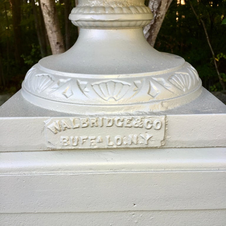 Large scale cast iron urn with handles on multi-tiered plinth base produced by the Walbridge Company of Buffalo, NY, circa 1900. See image 4 for detailed dimensions. Urn and plinths have been professionally sandblasted and powder coated a light