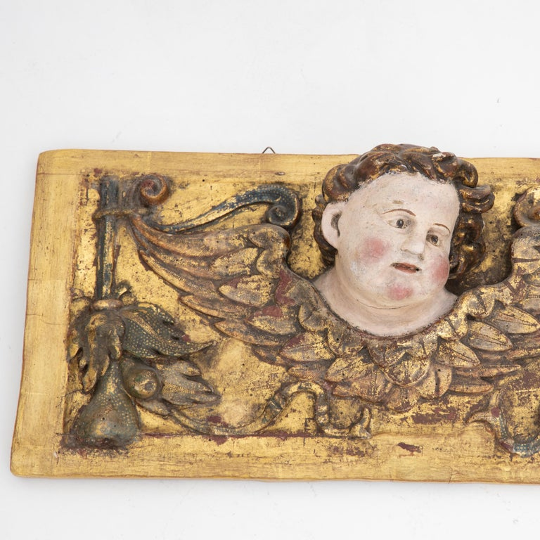 Rectangular wall appliqué with naturalistically painted angel heads with wings. Wood carved and gilded.