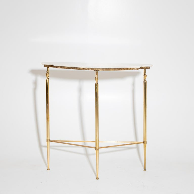 Small wall console with a light-colored stone top on a delicate brass frame with three legs and conical pinnacles.