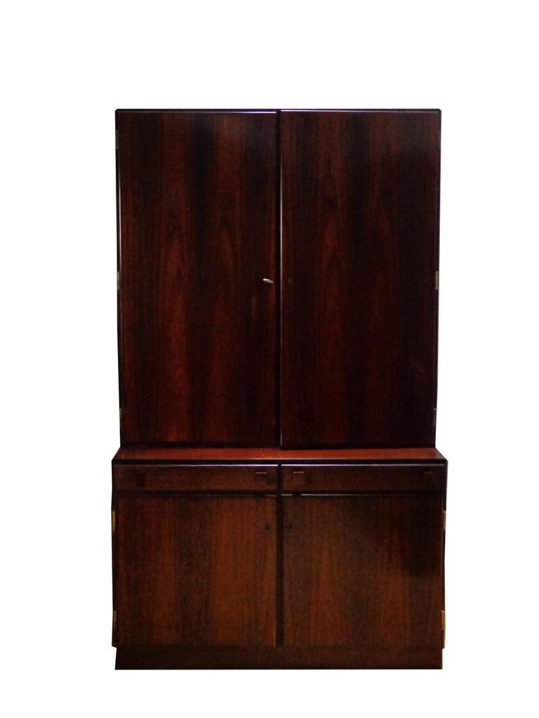 Wall unit of rosewood designed by Takashi Okamura and Erik Marquardsen, consisting base cabinet with doors and shelves inside. Top cabinet with pullout trays, shelves. Original keys included. Manufactured by O. Bank Larsen Møbelfabrik. Signed with