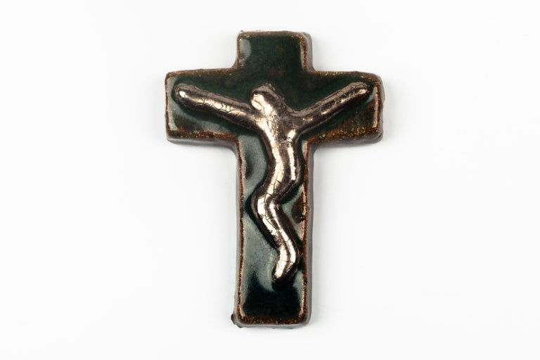 Preciously small crucifix in glazed ceramic, handmade made in Belgium in the 1970s. Glossy deep green and brown with metallic gold raised christ figure at its center.