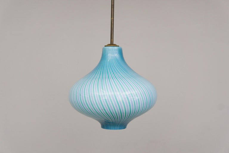 This bounteous pendant made of Murano glass has a unique flashed glass in a coloring in green and light blue which crate a beautiful glow when lit. The detailed yet minimal mounting is made of brass. Designed by Massimo Vignelli  Massimo Vignelli