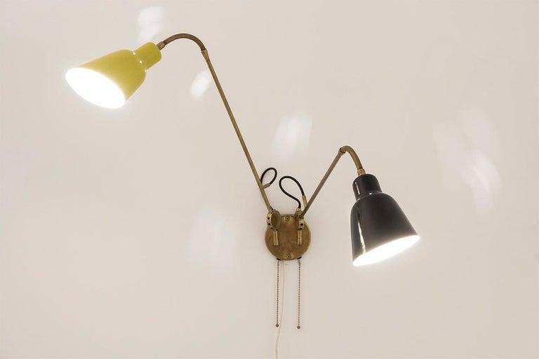 Wall light brass construction, flexible arms, reflectors yellow/black lacquered aluminium Dimension: L. 75 cm 1 arm Design Angelo Lelli, circa 1950 Manufacturer Arredoluce, Italy.