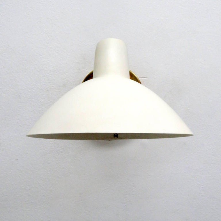 Wonderful 'Visor' wall light by Vittoriano Vigano for Arteluce designed in Italy, 1950s, egg shell colored enameled aluminium, brass, can be mounted in an upward or downward position, shade articulate left/right, on/off switch on the brass back