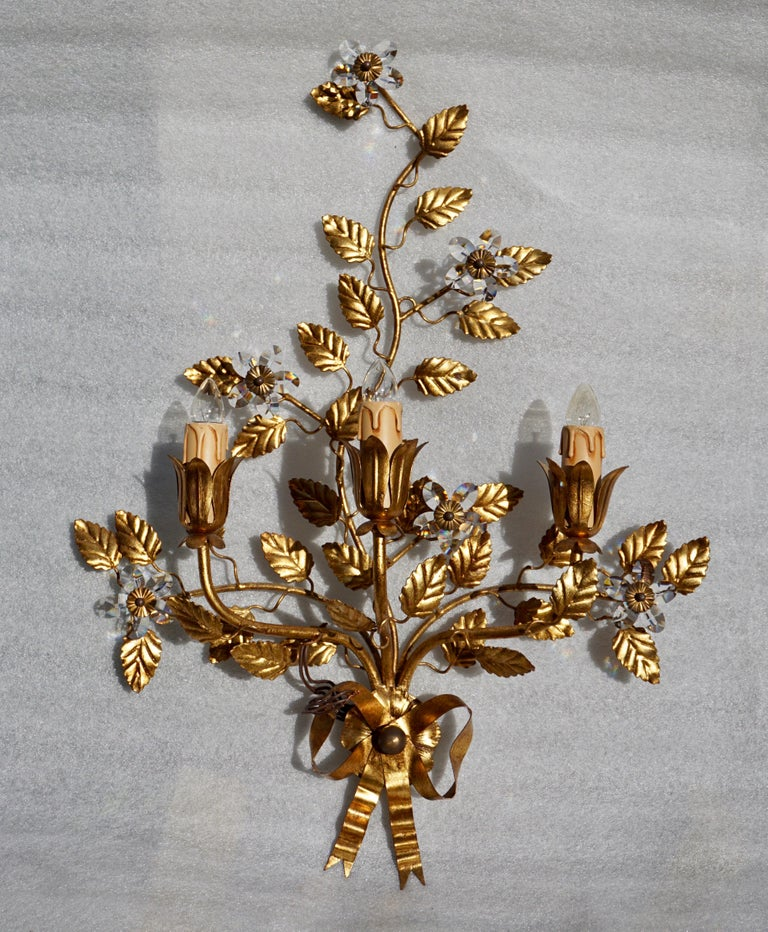 Brass gilded sconce with crystal flowers. Italy. Measures: Height 60 cm. Width 45 cm. Depth 17 cm. Tree E14 bulbs.
