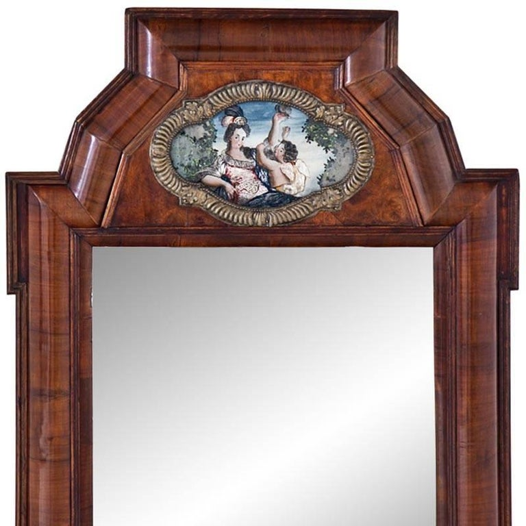 Rectangular wall mirror with a slightly curved walnut frame. The frame shows a polychrome depiction of Venus with cupid in a quatrefoil cartouche. Size of mirror glass: 40.5 x 35 cm.