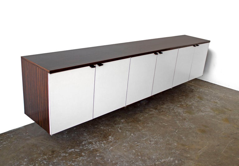 Custom-made wall mount credenza after Florence Knoll. The cabinet is an exotic rosewood laminate and the doors are white laminate. A large quality crafted piece with great style at an affordable price.