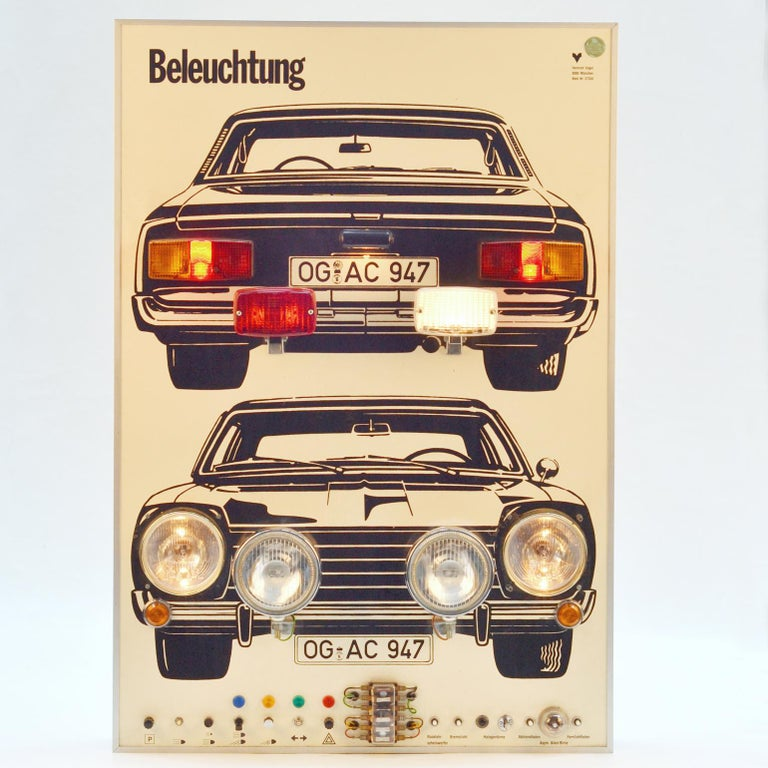 The wall mounted 1970's artwork demonstrating driving instructions about the use of car lights. The manual instruction panel at the bottom can be used to switch on the various car lights and learn about the function of the operation of the lights in