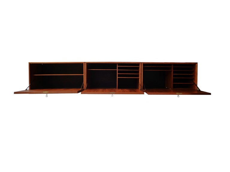 Wall-mounted cabinet of teak designed by Poul Cadovius, consisting three cabinets with door and shelves inside. Original keys included. Signed with paper makers plaquette.  Poul Cadovius created one of the world's first wall-mounted shelving