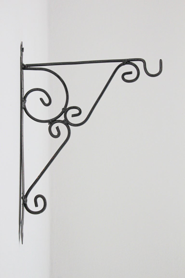 Hand crafted iron scroll design wall bracket.  Vintage wrought iron handcrafted wall-bracket for lanterns or signs. Perfect for hanging lights or plants outdoors. Scrolling wall-mounted iron brackets. Multiple available. Dimensions: Projection: