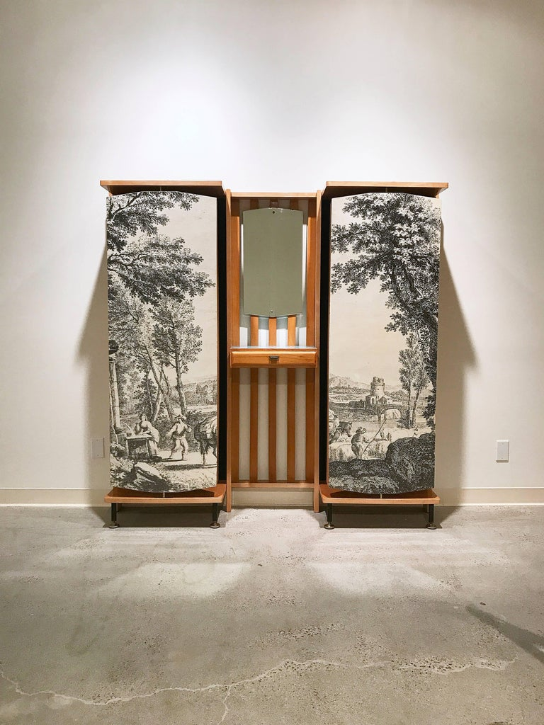 Incredible and rare wall-mounted entryway furniture piece by Enzo Strada with vanity mirror and drawer as well as rotating panels with coat hooks on one side and a bucolic transfer-printed scene on the other. The piece is veneered in maple