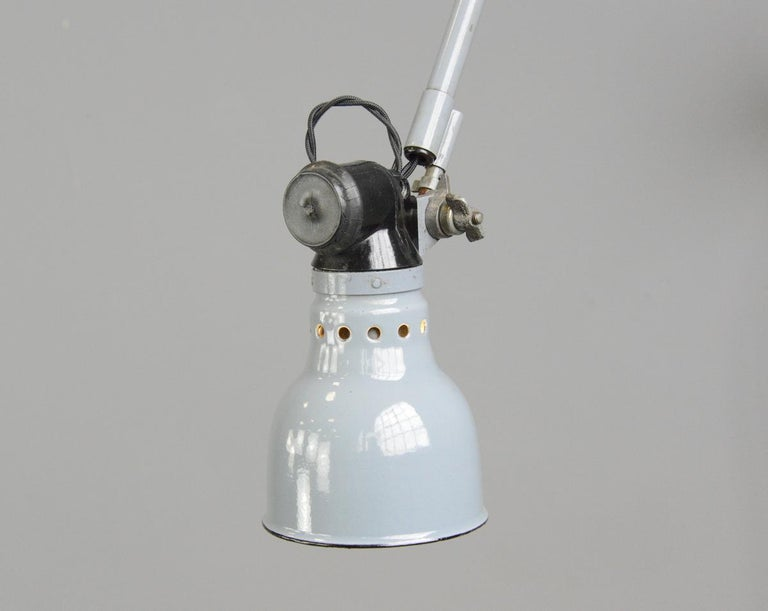 Wall mounted task lamp by Rademacher, circa 1930s  - Vitreous grey enamel shade - Bakelite switch - Takes E27 fitting bulbs - Tubular steel articulated arms - By Ernst Rademacher - German, 1930s - Shade measures 11cm wide  - Extends up to