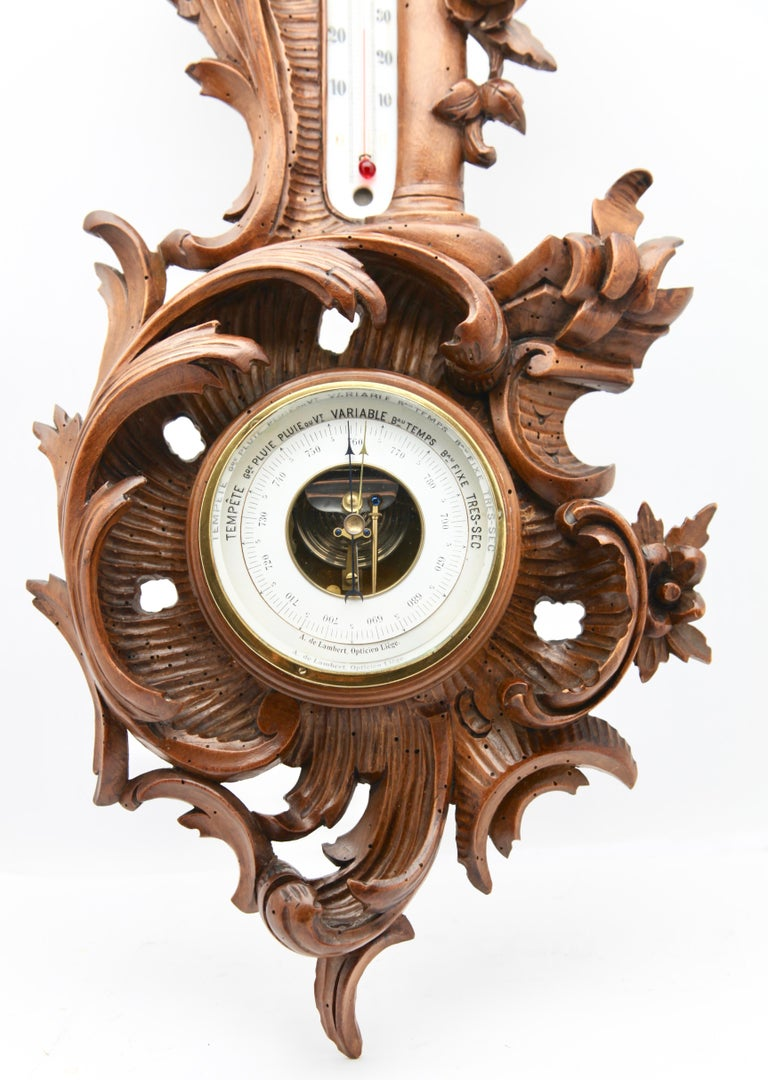 Wall-mounted weather station in carved walnut Made in Belgium by A. de Lambert. High quality mechanism with jeweled movement barometer and thermometer (in centigrade)