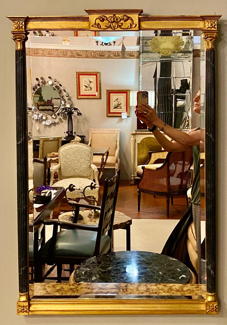An ebony and parcel gilt decorated pair of wall or console mirrors. These finely detailed neoclassical beveled glass mirrors have a clean center flanked with column-form sides. Terminating in a Federal star crested top.