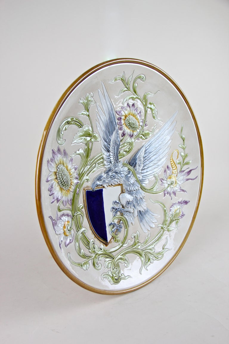 Majestic Majolica wall plate by Wilhelm Schiller & Son adorned by a blue eagle holding a blue/white coat of arms and a gorgeous floral design in relief. The late 19th century Majolica Plate was colored in light blue and green making it an impressive
