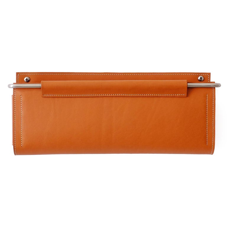 Crafted with saddle color vegetable-tanned leather and satin finished stainless steel, the Ledger Wall Pocket luxuriously hides away loose ends; from your remote control, to your mail, keys and iPad. These wall pockets/ magazine racks help keep