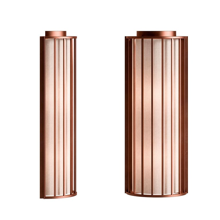 Old and new blend seamlessly together in this remarkable wall sconce that showcases a sculptural profile reminiscent of old lanterns. Marked by a cage-style cylindrical frame, this sconce is crafted of metal with a brushed-copper finish that