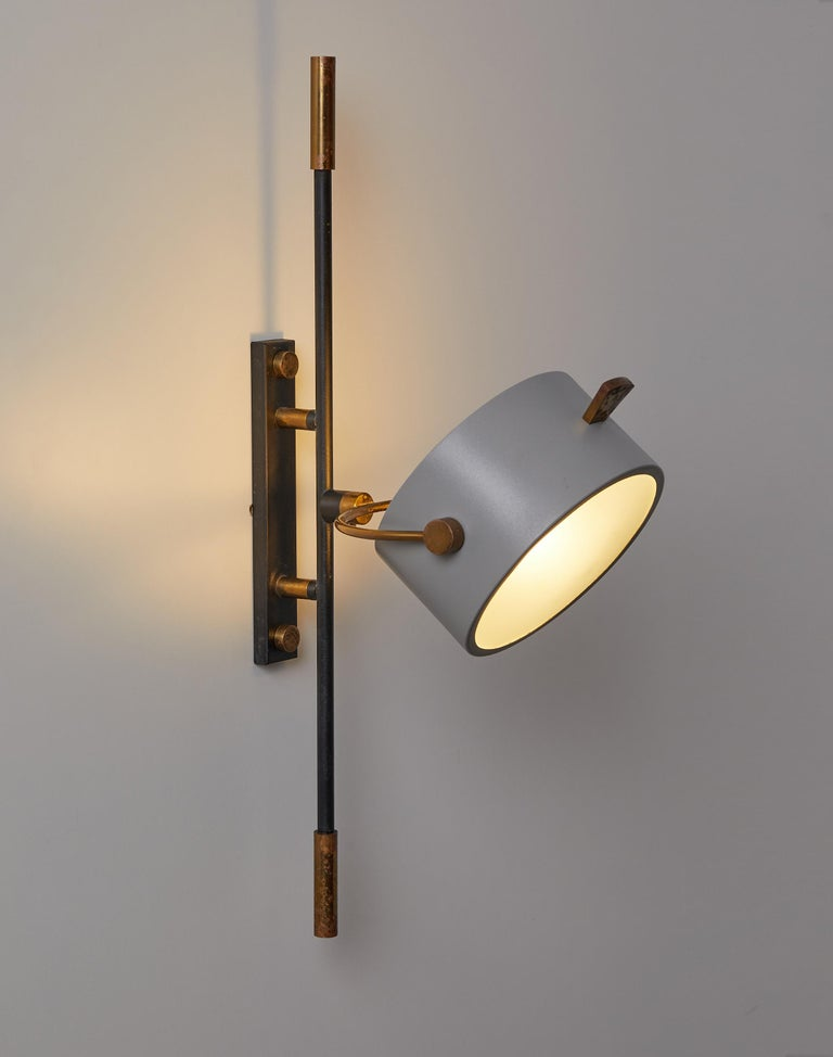 Wall sconce with lens shaped reflector by Maison Lunel, France, 1950  This elegant wall lamp is part of a rare series of wall lights having as a common element a circular reflector with curved sandblasted glass.  It is composed of a central rod