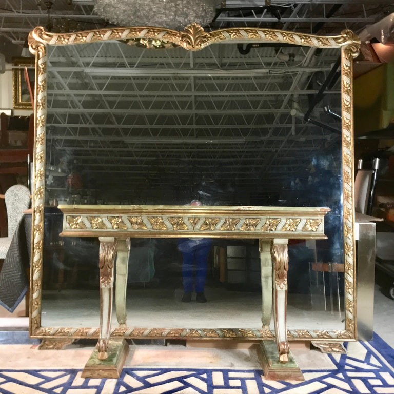 1950s vintage Italian carved, paint decorated and gilt wood framed mirror including a fixed green onyx top console table on two scrolled legs mounted on stepped onyx and gilt wood plinths. Mirror frame appears to float above the floor on two wing