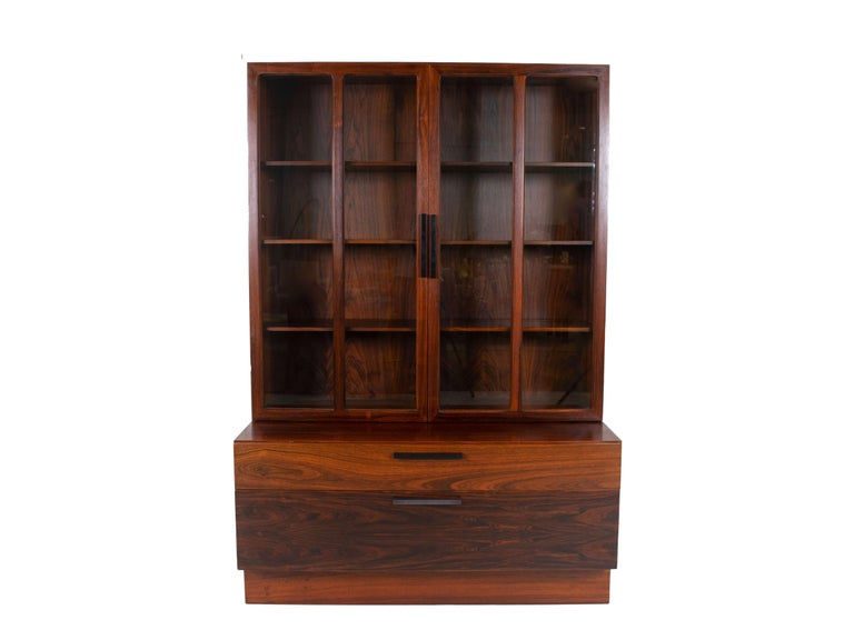 Wall unit by Ib Kofod-Larsen for Faarup Møbelfabrik in Rosewood from Denmark 1960s. This unit consists of two elements that are not connected; a display cabinet and a cabinet with two drawers. The display cabinet has two doors with glass and black