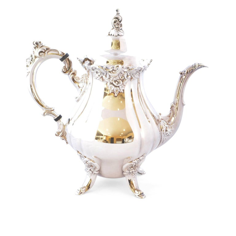 Stunning Wallace silver plate four-piece set with Baroque pattern is truly timeless and holds its own in the most formal settings. The set includes coffee pot and teapot, both with hinged lids, creamer and sugar bowl with matching lid. The