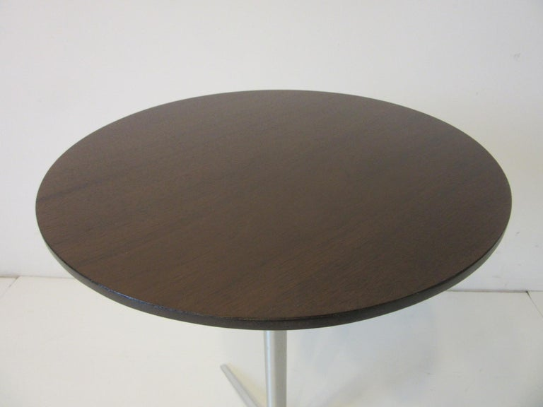 A very slim cigarette / drink side table with round walnut top and brushed aluminum star base retaining the original manufactures label by Thonet NYC. Perfect side table next to that lounge chair or a table for a tight space.