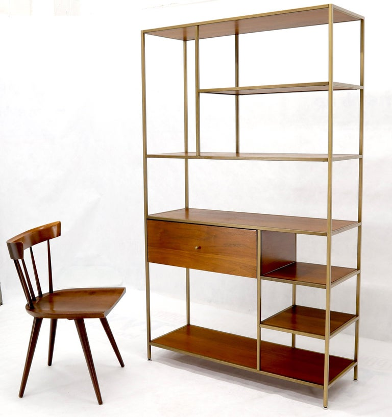 Mid-Century Modern style walnut and brass staggered étagère shelving unit. One deep drawer compartment.