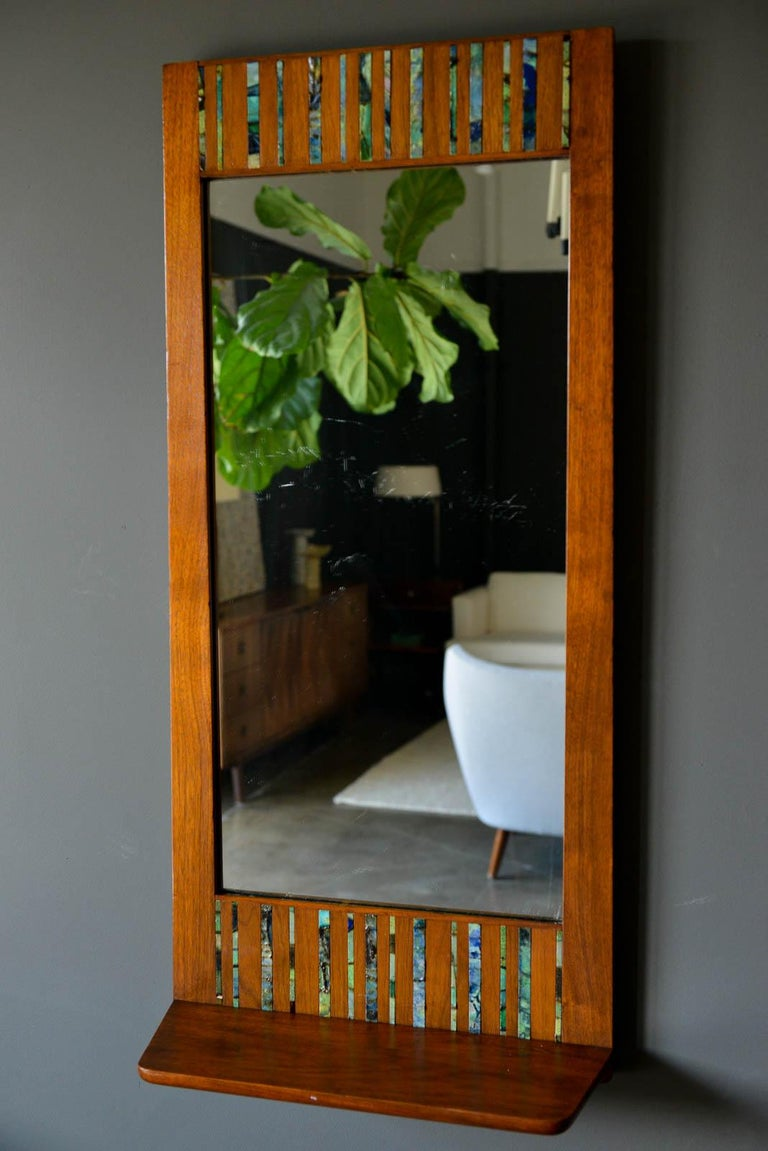 Walnut and ceramic tile floating shelf mirror by Harris Strong, circa 1965. Beautiful walnut frame with original mirror and handmade blue/green/aqua ceramic inlay tiles. Excellent original condition. Slight patina to the mirror, wood is excellent