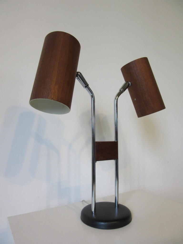 An adjustable swiveling double-headed table lamp with walnut veneer wrapped cylinder shades mounted on polished chromed stems held together by a piece of walnut with a satin black metal base. The three-way light switches to the tops of each cylinder