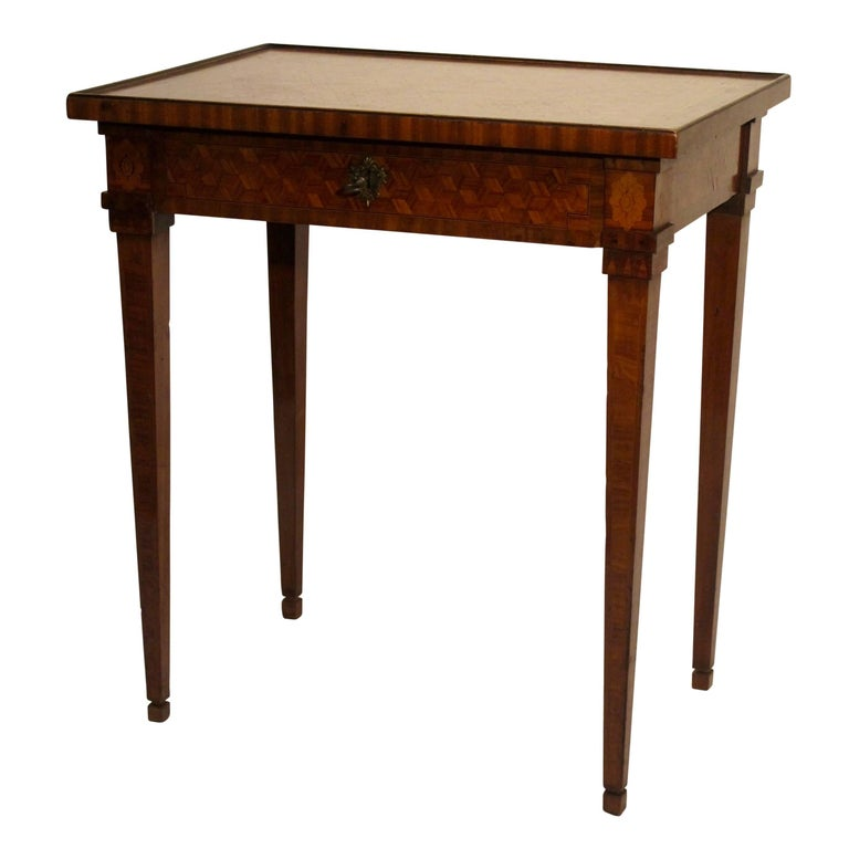 Exceptional walnut and mixed fruitwood table with inlay parquetry design and beautiful detailing, having a single center drawer and standing on tapering legs. In superb original condition, France, late 18th century, circa 1780.