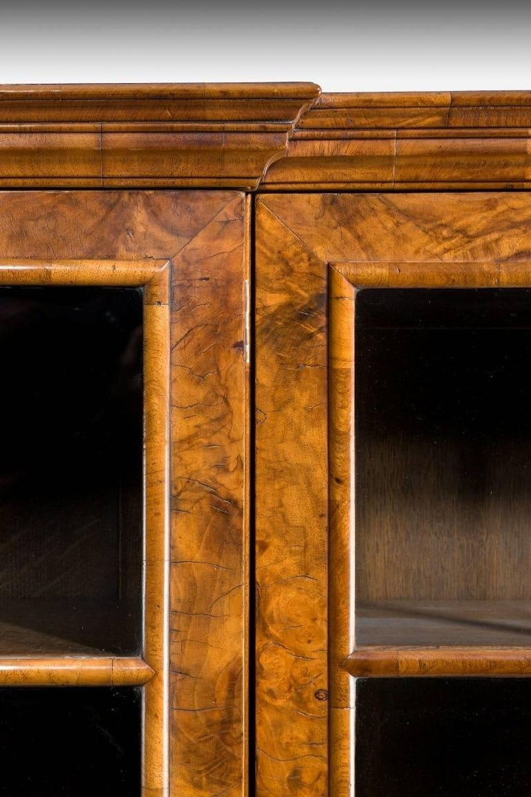 A good quality walnut and oyster veneered Peeps style breakfront four door bookcase of small proportions. The glazed four doors above three draws, two short and one longer to the centre all veneered in oyster venues. All shelves are fully