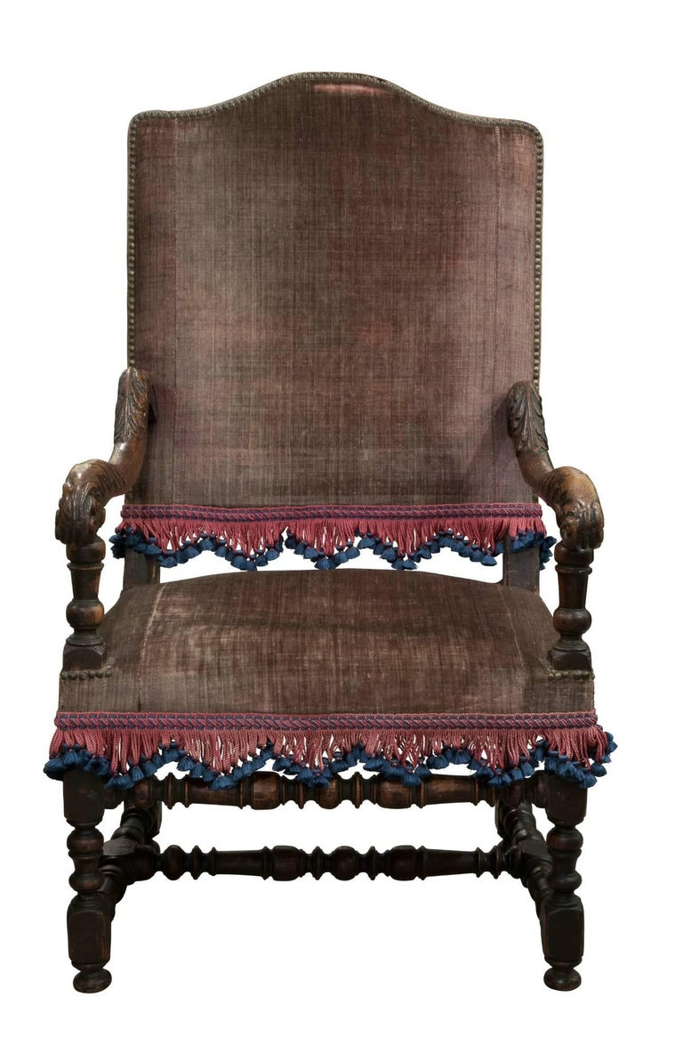 French Walnut armchair with humped and upholstered back above scrolled and carved arms with stuffed seat on turned legs and stretcher,  circa 1700.   Measure: Seat height 41cm.