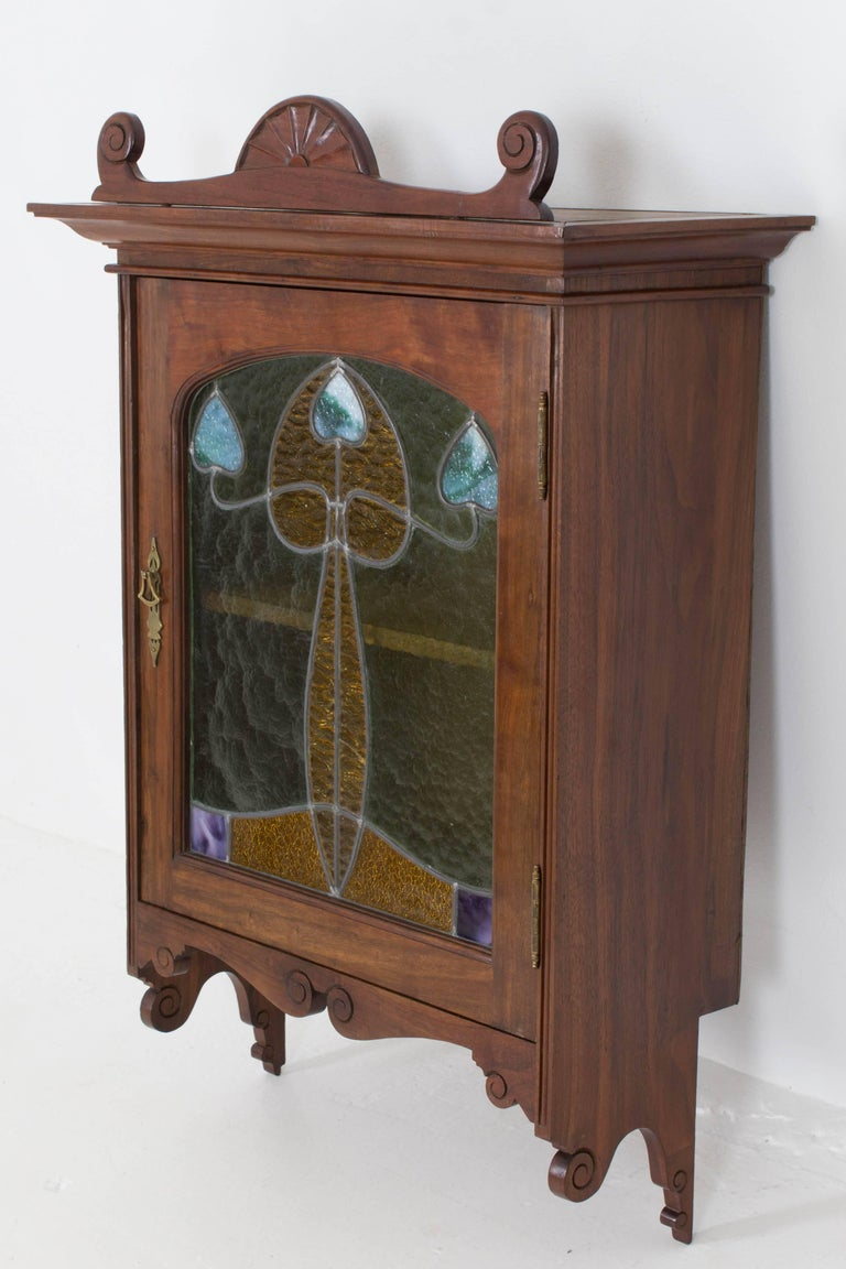 Magnificent and rare Art Nouveau wall cabinet. Striking French design from the 1900s. Walnut with original stained glass. Original brass handle. In very good condition with minor wear consistent with age and use, preserving a beautiful patina.