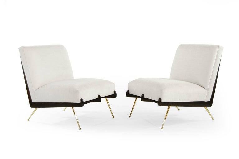 A phenomenal pair of lounge chairs in the style of Italian designer Gio Ponti, circa 1950s.  Boomerang shaped walnut frames fully restored to their original dark finish, newly upholstered in off-white velvet. Thin tapered brass legs newly