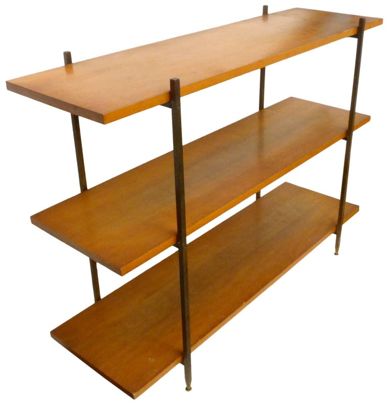 An elegant shelving unit in walnut, brass and iron by Milo Baughman for Murray Furniture Co. Classic, midcentury, stylish simplicity; three evenly-spaced and sized walnut shelves held by a square-stock, machined, brass and iron frame, the legs