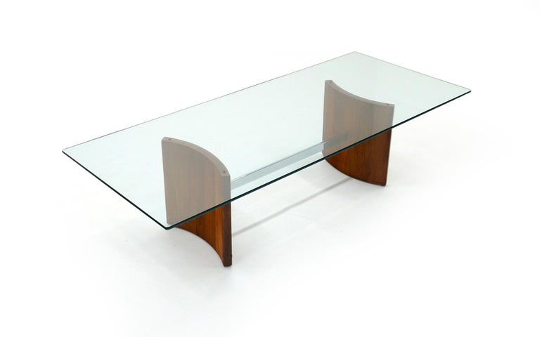 Vladimir Kagan coffee table. Curved walnut supports connected by a chrome bar supporting the original glass. Very good condition.
