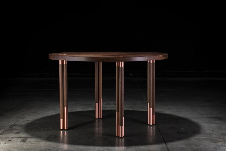 With the use of copper inlays and solid walnut, the Canfield dining table was created with an elegant and modern look. With handcrafted copper and walnut legs, this piece can stand out and be a featured piece of many different rooms.