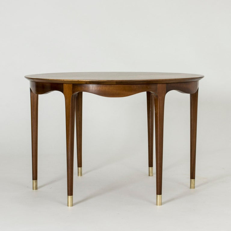 Stunning walnut coffee table by Ole Wanscher, with a beautiful wavy rim and brass feet on the six legs.