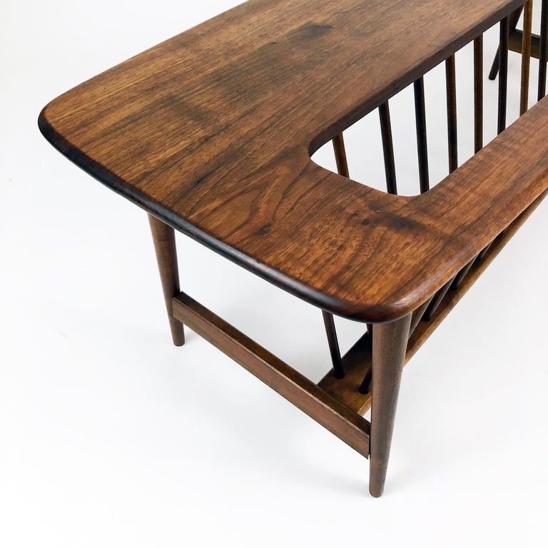 This beautifully-grained dark walnut coffee table by Arthur Umanoff for Washington Woodcraft incorporates a large rack for magazines or coffee table book display.